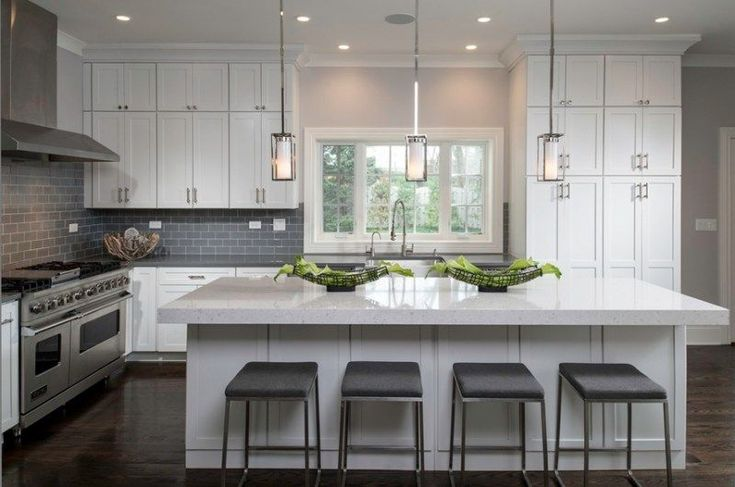White kitchen with gray upholstered bar stools and gray backsplash. Kitchen with tube pendant lights over white kitchen island with laminate countertop
