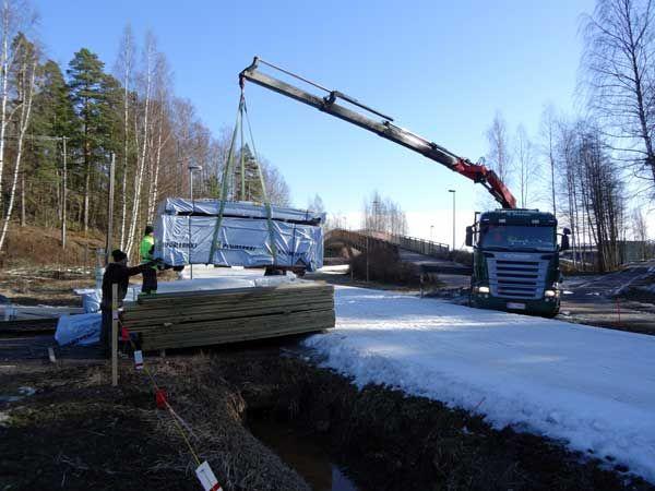 Rakentaminen Leppävaarassa jatkuu. Lumetettu latu houkuttelee vielä hiihtäjiä, vaikka maa muuten on paljaana. Puutavara nostetaan ladun yli.