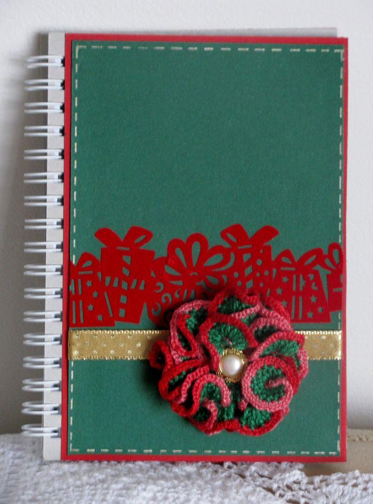 Vánoční zápisník se snímatelnou broží Zápisník je dekorován barevnými papíry, zlatou stužkou, červenou bordurou a háčkovaným snímatelným 3D květem s knoflíčkovým středem. Květ - brož je opatřen brožovým můstkem.