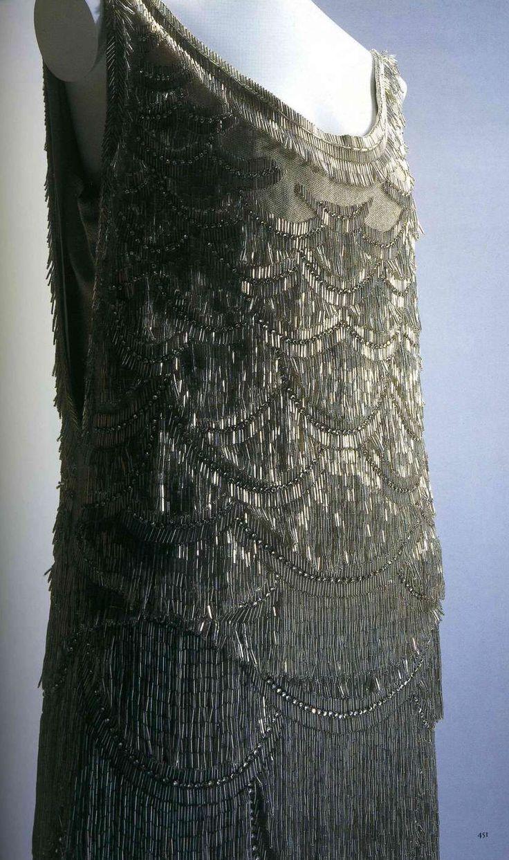 Вечернее платье. Ворт, около 1927. Бежевый шелковый тюль, бахрома из серебряного бисера по всему платью, нижнее платье с серебряной вышивкой с цветочным узором и бахромой из бисера по краю юбки.
