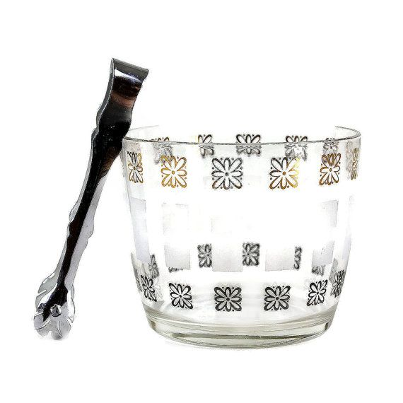 This cheerful glass ice bucket features a kitschy pattern of gold and black daisies with frosted white rectangle bands. Bucket, made in the