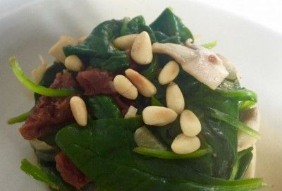 Spinazie uit de wok met champignons, zongedroogde tomaatjes en pijnboompitten