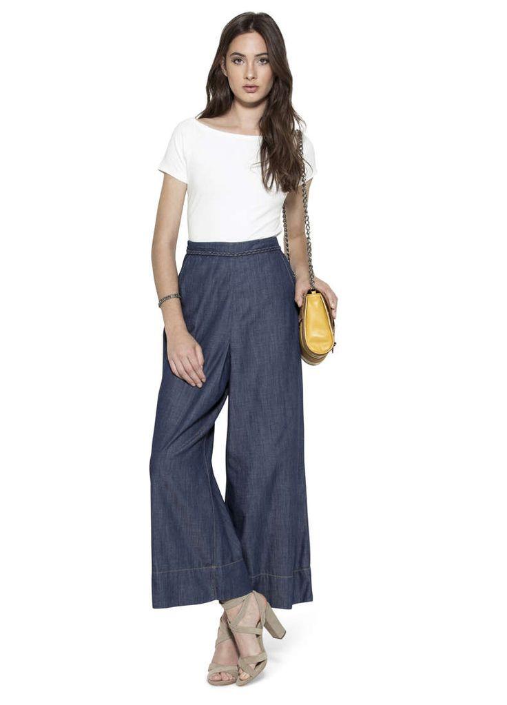 Calça saia índigo com comprimento até o tornozelo, possui detalha de tecido trançado no cós, bolsos frontais e fechamento através de zíper e abotoamento nas costas. É uma saia mode