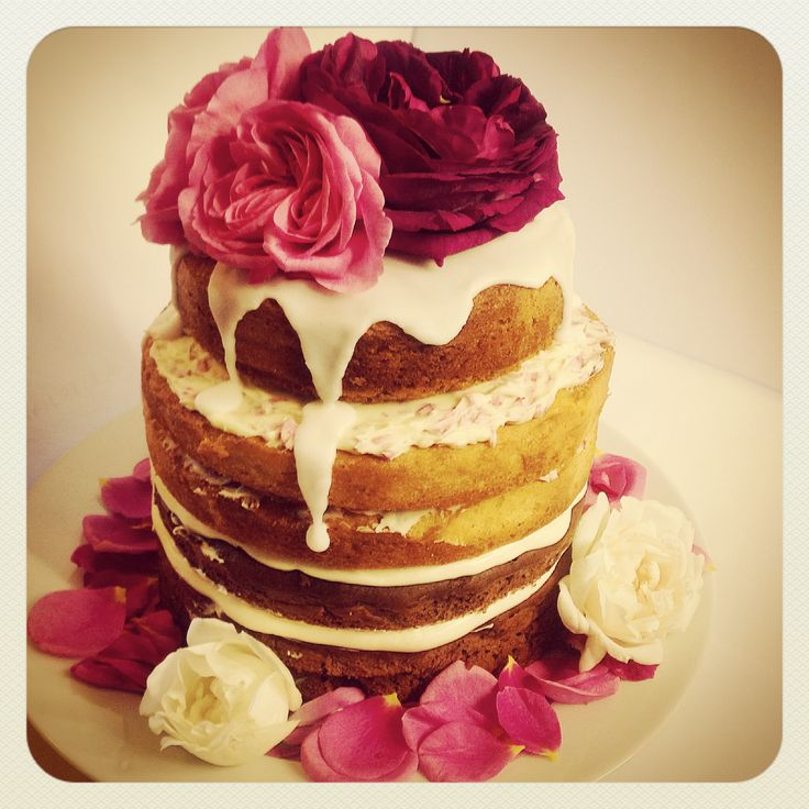naked cake of red velvet on the bottom, vanilla rose on the top, decorated with whole edible roses available from greensofdevon.com