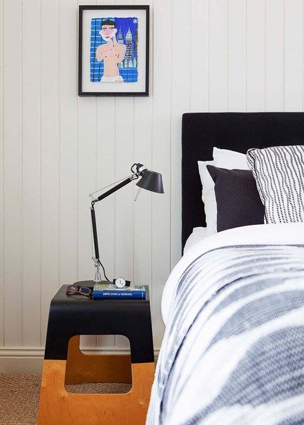A stool was paint-dipped  to create a bedside table that echoes the main bedroom's black-and-white theme, which is continued in collected curios throughout the home.