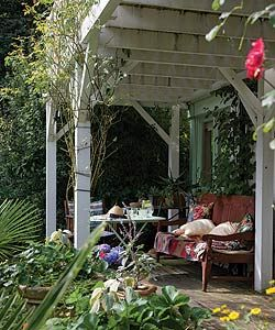 Old furniture with cushions and throws turn a verandah into a cosy outdoor room