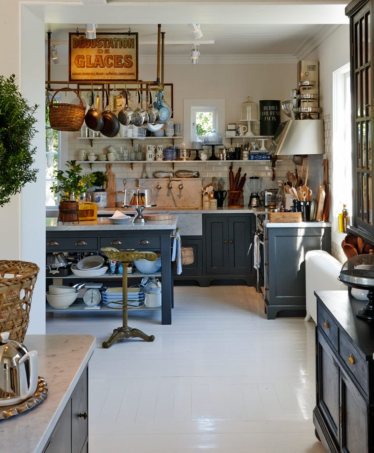 everything, everything about this overstuffed kitchen - marble, brass, hanging things, wicker, more than enough, a box of pepper grinders, open shelving, tiers things, fancy toaster, teeny tiny lemon tree, stands for all my cakes and enough wooden spoons for all of the bad kids