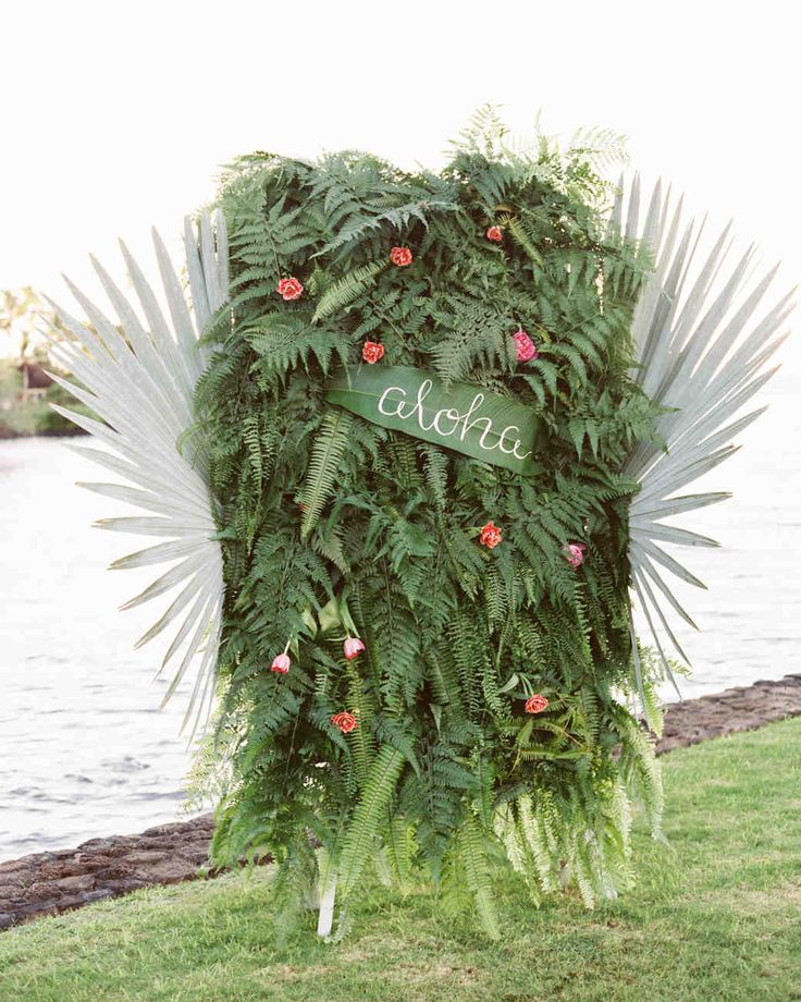 A Casual Beach Wedding in Puako, Hawaii | Martha Stewart Weddings - The couple's planner designed a photo backdrop with live ferns, palm leaves, and other plants native to Hawaii, which showcased the natural beauty of the islands. #weddingideas #photoboothbackdrop #beachwedding #weddingflowers
