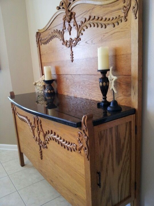 Old bed repurposed as a sideboard, cabinet doors on both ends for storage.
