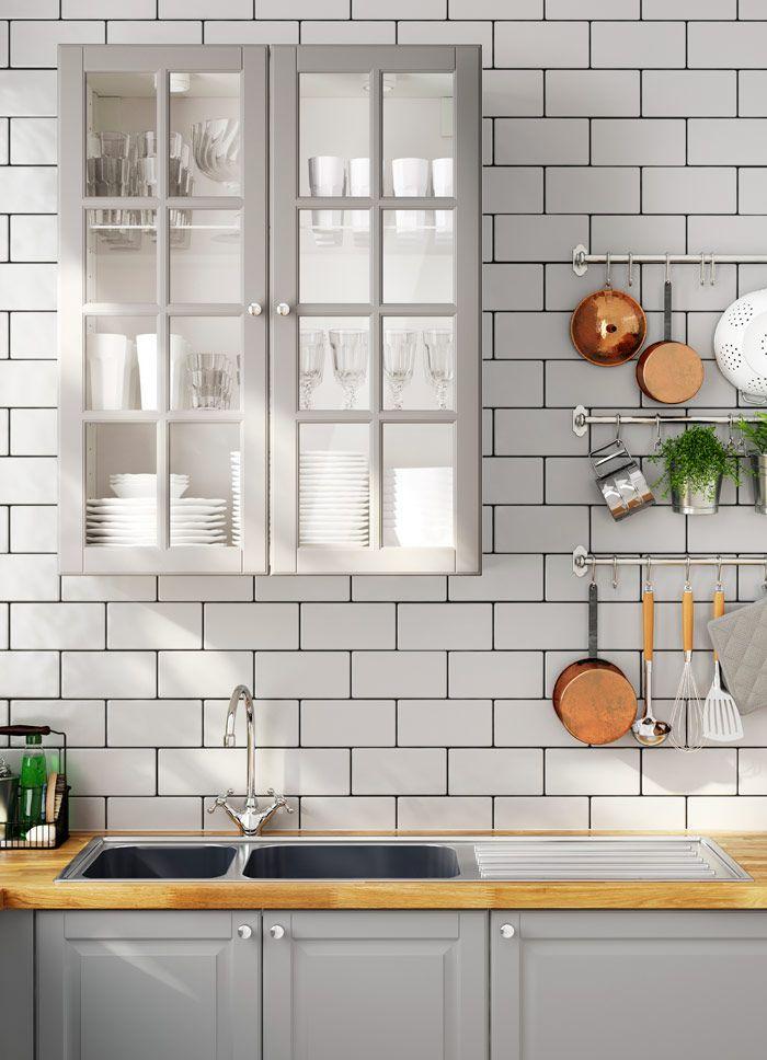 Traditionellt grått IKEA kök med bänkskivor i trä, vitrinluckor och blandare i traditionell stil