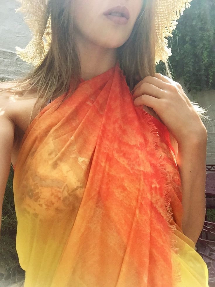 Alison is wearing the big orange scarf as a dress for her beach day. Convenient and stylish, it's definitely the accessory for your summer styles!