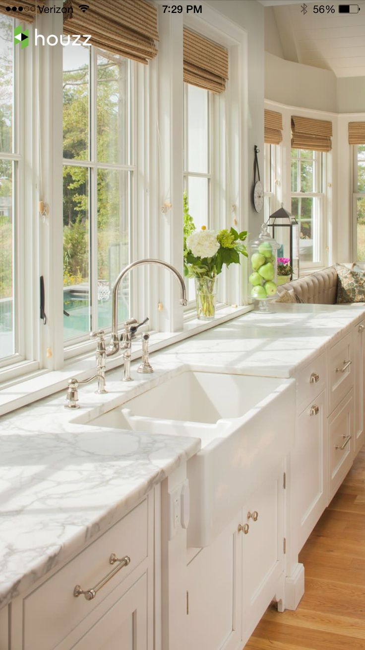 Love the natural light, white cabinets and double basin sink; would do a marble look alike in quartz to cut down on maintenance