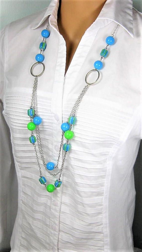Blue and green multi strand necklace handmade by Ralston Originals. This beaded necklace is made with large round turquoise and lime green acrylic beads, large multi colored turquoise and lime green acrylic beads, and silver acrylic beads. The use of acrylic beads makes this necklace
