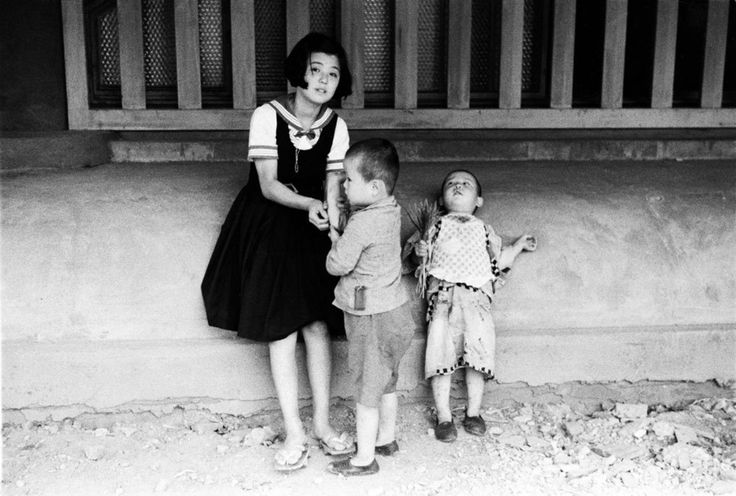 Kineo KUWABARA : children in front of building on dirt road. Japan. Undated.