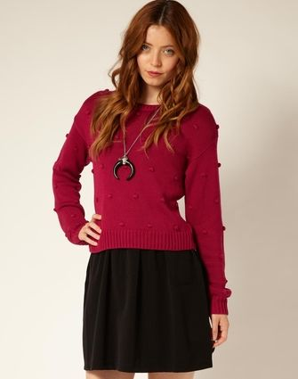 This sweater has spots with the contrast of the same color base sweater material.