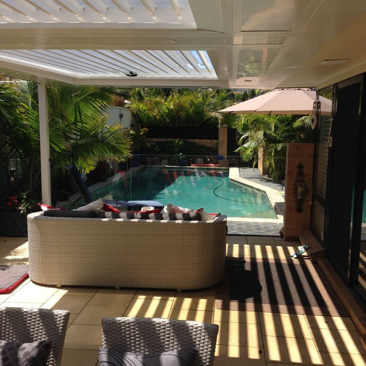 Tiled outdoor living area with opening roof, glass handrail and access to the pool.