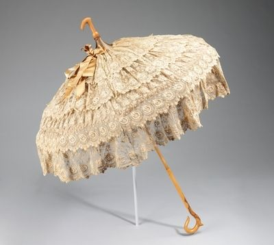 Lace & ruffled parasol, ca 1885.    When a Victorian lady rode in an open top carriage or strolled outdoors, she always kept her parasol up and on display. The parasol was trimmed with an assortment of materials, such as silk tassels or cotton lace, and made specifically to complement certain outfits!
