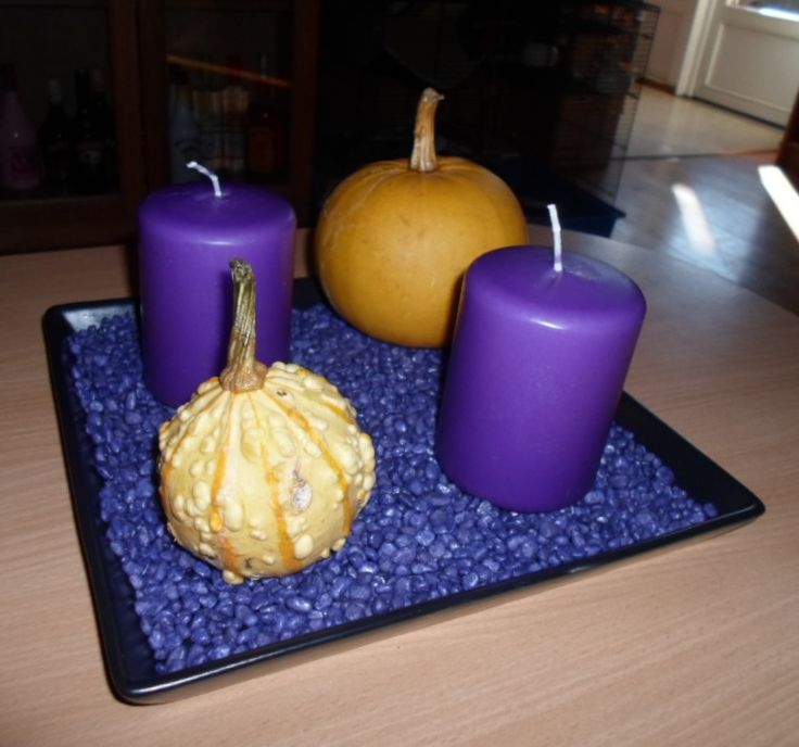 Halloween decoration with purple candles, purple stones and two pumpkins.