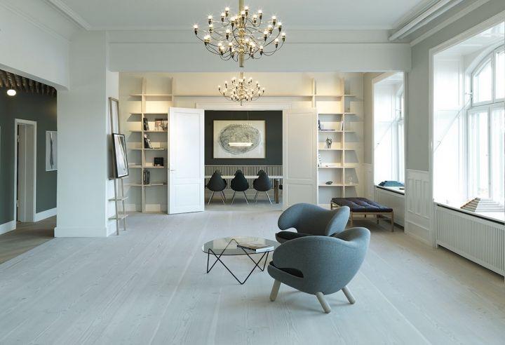 Nel salotto dello showroom Dinesen a Copenhagen, Pelican Chair by Raf Simons per Kvadrat, divano OW150 di Carl Hansen by Hans Wegner e Pedrera Coffee Table di Gubi firmato Barba Corsini