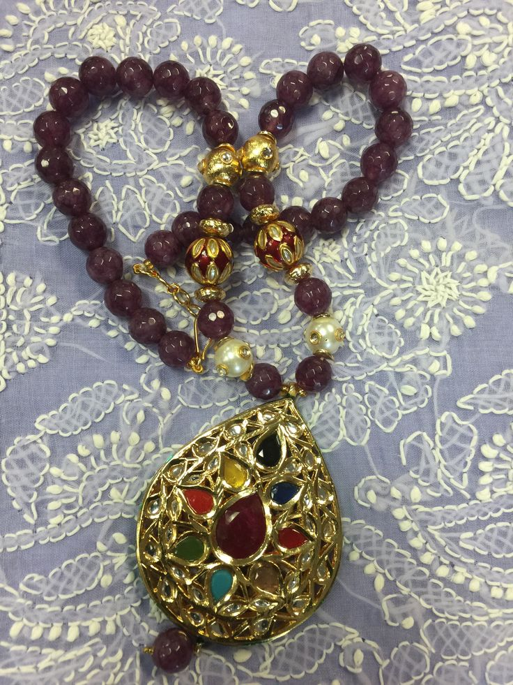 Give up yourself for the party with a Enamel (Meenakari) Kundan Pendant set is studded with Stones and there is a beautiful Floral design surrounding it. There is a string (Mala) with stones and pearls.