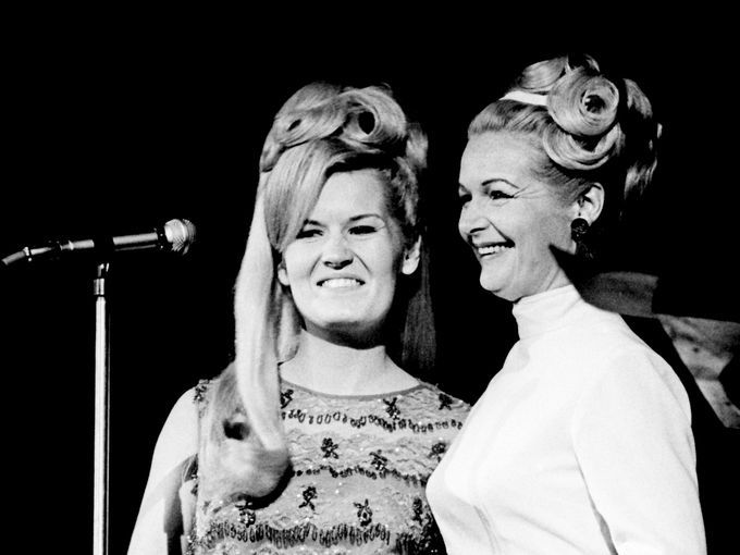 "Lynn Anderson, left, and her mother, Liz Anderson, stand before the microphone at RCA Victor's Opry breakfast Oct. 22, 1967. Singer and writer Liz Anderson told the audience she wasn't going to sing, but just wanted to introduce her daughter, who appears on ""The Lawrence Welk Show."""