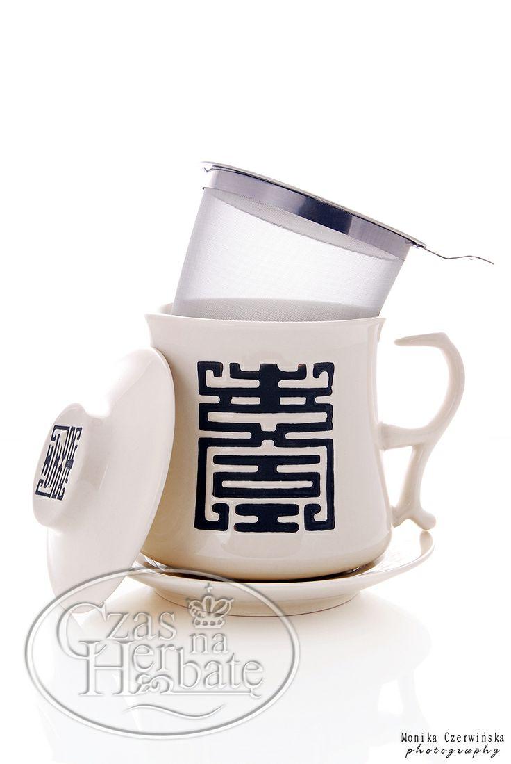 Stylowy zestaw do herbaty składający się z kubka z zaparzaczem, talerzyka oraz przykrywki. Elementy są zdobione orientalnym ornamentem.