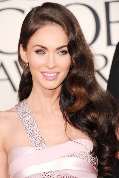 "Megan Fox' Side-Swept Hair @ Golden Globes 2011:  To create Megan Fox's cascading waves, hairstylist Andy LeCompte began by blowdrying her hair with a volumizing mousse and doing a curl set using a 3/4-inch iron. After smoothing ringlets with a brush, he parted hair to the side and tucked a section behind Fox's ear. ""I used a dab of Oribe Gel Serum to keep the section in place,"" he says."