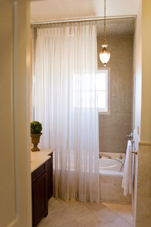 Add subtle privacy in a master bath with a sheer panel that will allow light to enter the space, but diffuse images on the other side of the sheer curtain panel.