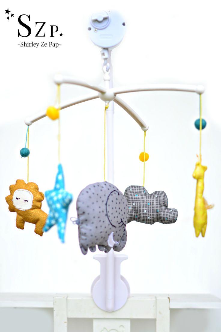 Mobile musical tournant sur potence, thème savane avec éléphant, lion, girafe et étoile. Fait main en France. Mobile à accrocher sur le lit à barreaux de bébé. Shirleyzepap