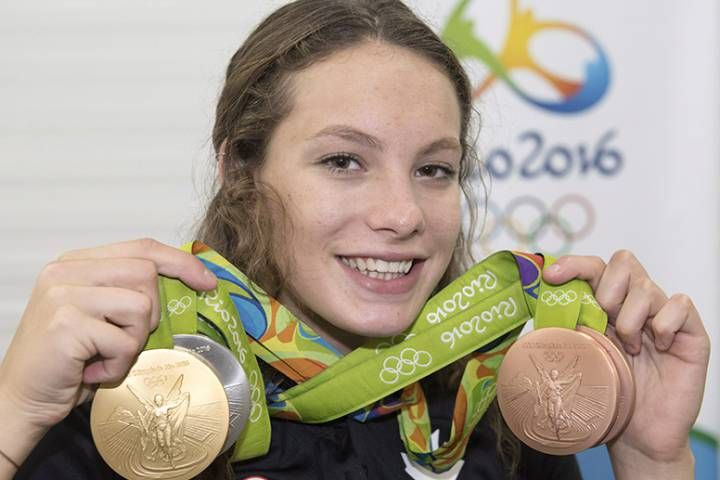 Penny Oleksiak holds up the four medals that she has won over the course of the 2016 Rio Olympics.
