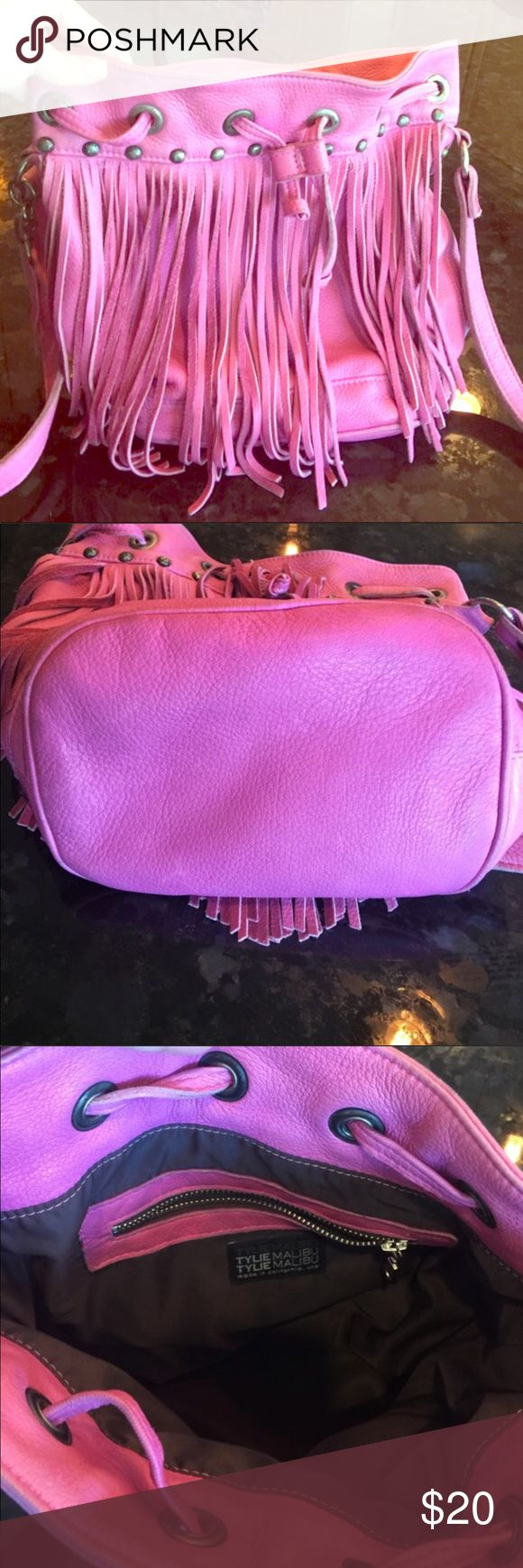 Pink leather fringe bucket purse Tylie Malibu brand. This awesome boho purse is a fun hot pink leather drawstring bucket style lined in fringe and studs. Adjustable long handle let's you wear it over the shoulder or as a crossbody. Condition is pre-loved but good, there are 2 minor marks but the fringe covers them(see last 2 photos)and the interior is very clean. The strap shows some wear but doesn't look bad. Hence the great price discount for this brand name bag.Overall A fun boho purse…