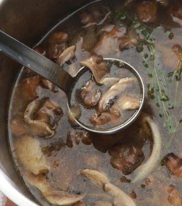 Σε μια κατσαρόλα, σε δυνατή φωτιά, προσθέτουμε το ελαιόλαδο και σοτάρουμε το κρεμμύδι μέχρι να μαλακώσει. Προσθέτουμε το σκόρδο και τα μανιτάρια και συνεχίζουμε το σοτάρισμα μέχρι να μαλακώσουν και αυτά. Σβήνουμε με το κρασί και προσθέτουμε το ζωμό. Σιγοβράζουμε, ξαφρίζοντας για 45 λεπτά περίπου. Σουρώνουμε από ψιλή σήτα, κρυώνουμε γρήγορα και διατηρούμε στο ψυγείο.