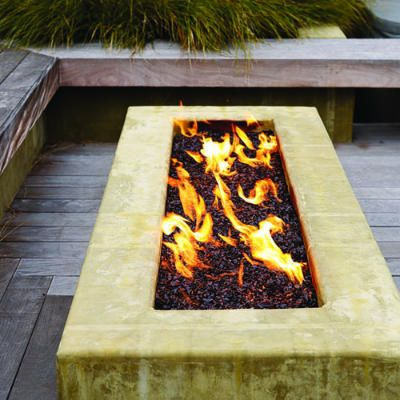 A raised concrete trough filled with recycled glass keeps the dining deck warm on cool nights. When not in use, the gas firepit can be covered with a slab of ipe wood, which converts it into a coffee table.