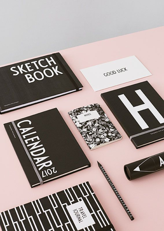 Create a black and white home office design with mixed stationery. On the picture: Sketch Book, 2017 Calendar, Personal notebook, Travel Journal, Occasion card, Pencil, Flowers by AJ notebook and crayons. Typography: AJ Vintage ABC.