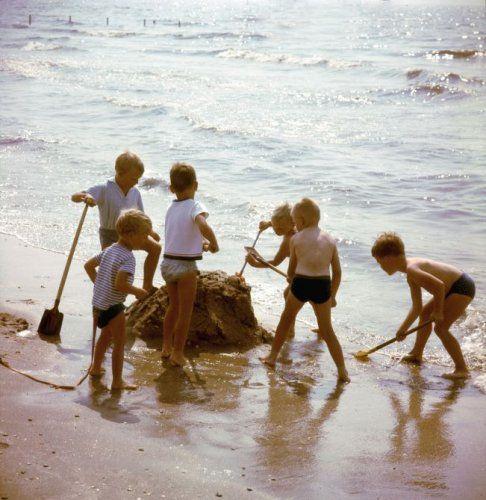 Jongens bouwen een zandkasteel op een strand. Plaats onbekend.[omstreeks 1966]