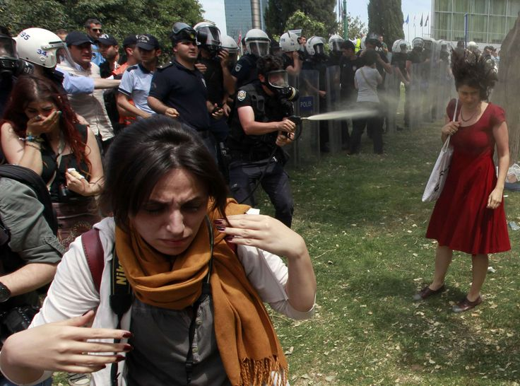 A Turkish riot policeman uses tear gas as people protest against the destruction of trees in a park brought about by a pedestrian project, in Taksim Square in central Istanbul May 28, 2013. REUTERS/Osman Orsal (TURKEY - Tags: POLITICS CIVIL UNREST ENVIRONMENT TPX IMAGES OF THE DAY)