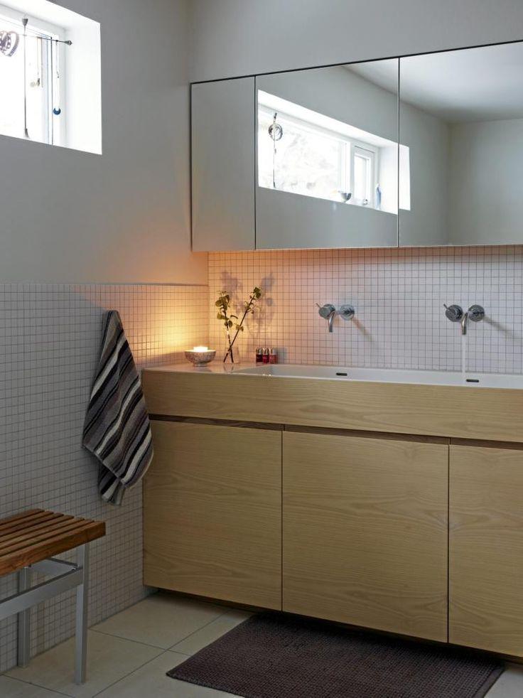 Sart og sobert. Badet er dust og enkelt, innredningen i tre gir varme til rommet. Kanten ved vasken og dørene er laget av samme stykke tre. Armaturene fra Vola ble i sin tid tegnet av Arne Jacobsen.