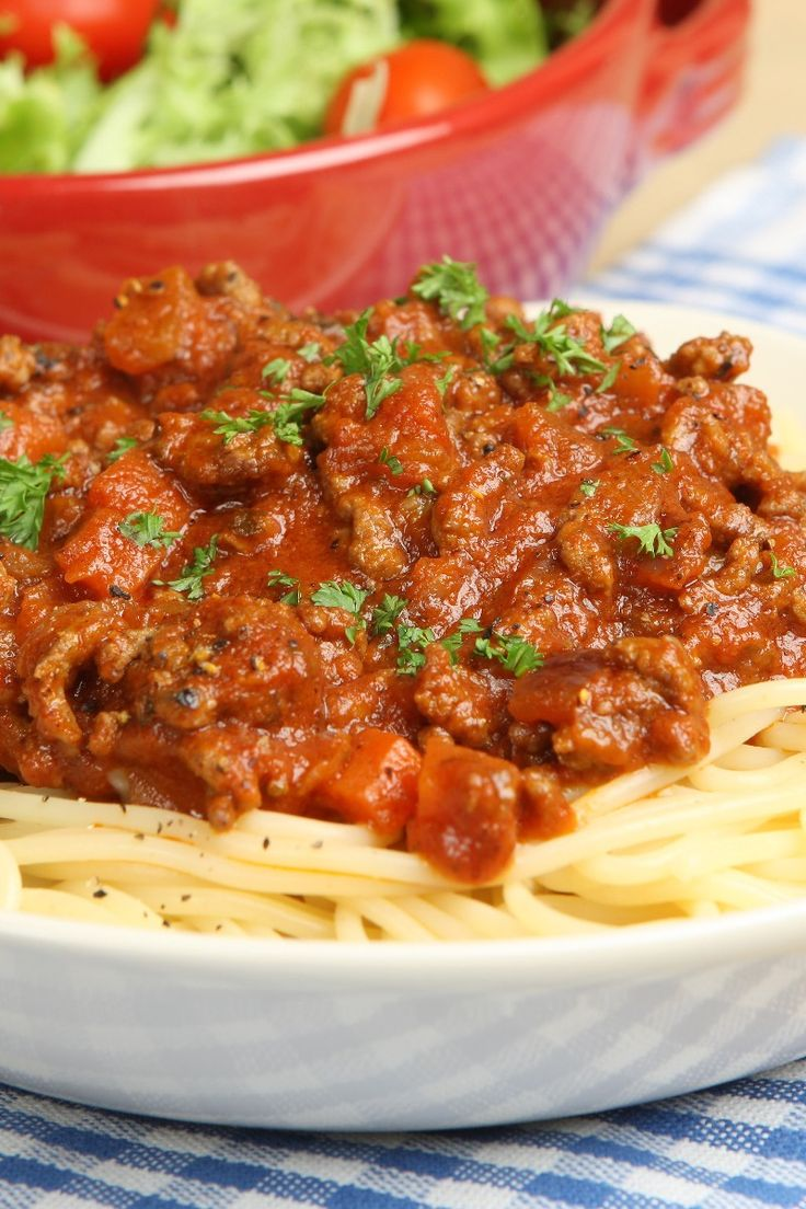 Recipe including course(s): Entrée; and ingredients: basil, black pepper, brown sugar, diced tomatoes, dried parsley, garlic cloves, onion, parmesan cheese, red pepper flakes, red wine, salt, sausage, spaghetti, tomato paste, tomato sauce, water