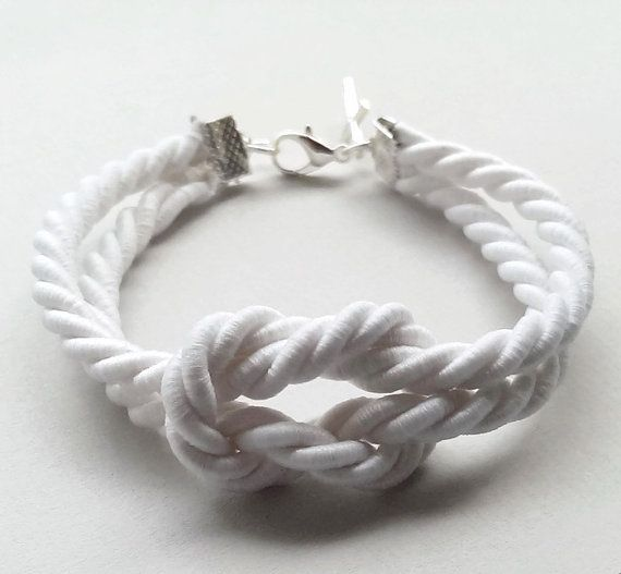 White nautical bracelet made of triple rope and decorated with a silver metal cross.
