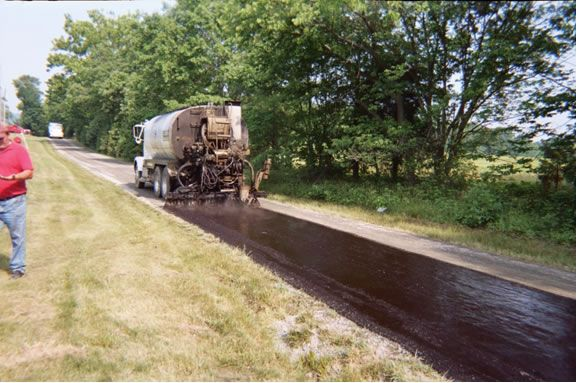 First a coat of liquid A/C is applied to the existing surface. This is accomplished by using a computer-controlled distributor truck equipped with spray bars, to apply an exact and consistent amount of liquid A/C, heated to the right temperature. Tar & chip, provides a beautiful rustic alternative to asphalt, with the look and feel of a country gravel road. #Pavement #chip_paving_installation #driveway