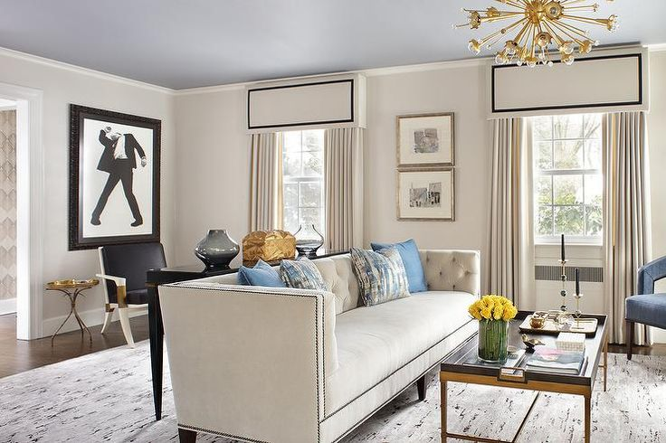 A Jonathan Adler Sputnik Pendant hangs from a gray ceiling over a brass tray cocktail table placed on a gray rug in front of an ivory sofa topped with blue pillows in this beautifully appointed ivory living room with blue accents. Cornice boxes