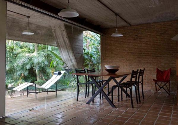 Nero e legno, un abbinamento perfetto per questa abitazione in Brasile. Il tavolo e le sedie (come la Tripolina appoggiata al muro) sono della collezione Futon Company, il negozio che i proprietari di casa - francesi di origine - hanno aperto a San Paolo.