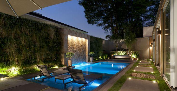 Projetada pela arquiteta Débora Aguiar, essa moderna área externa conta com palmeiras e arbustos ao redor da piscina, iluminados fazem fundo à área de descanso que fica próxima ao SPA. A piscina com cascata recebeu iluminação que, com o movimento das águas, confere brilho especial ao espaço.