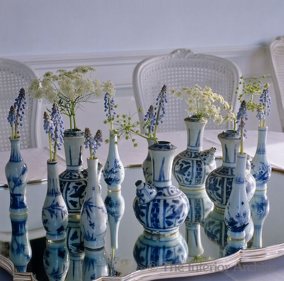 Axel Vervoordt ~ A collection of blue and white Chinese porcelain vases on a mirrored tray each hold a flower