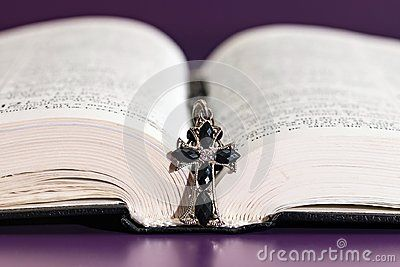 Holy Bible opened with an elegant old cross on top closeup, purple table.