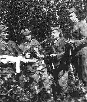 """Stoją od lewej: Stanisław Roszkowski """"Tarzan"""", ppor. Witold Buczak """"Ponury"""", Lucjan Niemyjski """"Krakus"""" - d-ca patrolu w oddziale """"Huzara"""", 22.VIII.1952 otoczony przez grupę operacyjną UB popełnił samobójstwo, Franciszek Łapiński """"Szwed"""" - 24.XII.1947 ciężko ranny w walce z grupą operacyjną UB-MO-KBW, dobity bagnetami. Uzbrojeniem żołnierzy jest bardzo rozpowszechniony w oddziałach powojennego podziemia niemiecki Stg-44 kal. 7,92 mm."""