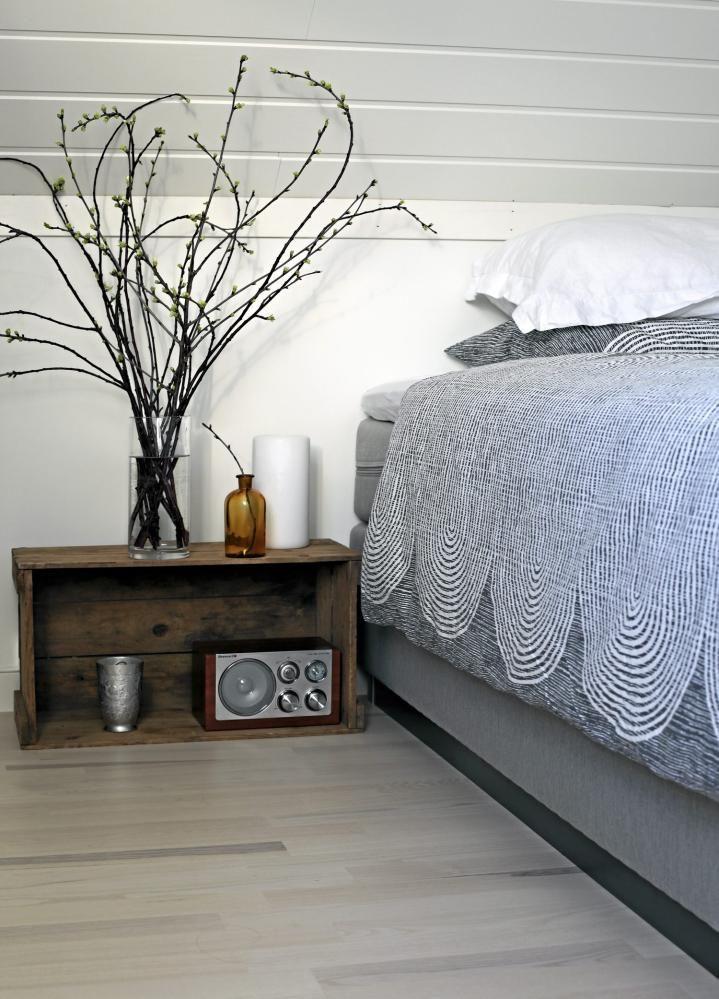 Soverommet preges av duse farger, i kombinasjon med geometriske former, her i form av et sengeteppe. Den gamle trekassen fungerer som et sjarmerende lite nattbord.