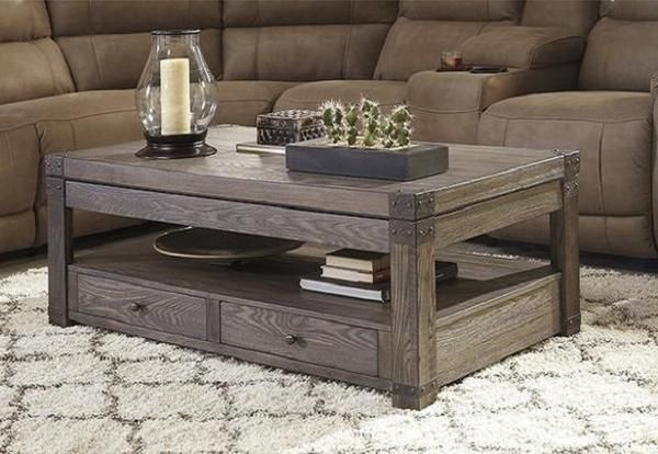Resembling turn-of-the-century campaign furnishings, Burladen lift top coffee table is a subtle nod to British Colonial style. Washed finish and weathered metal details reinforce the vintage vibe. Lift-top functionality makes dining and working in front of the television a breeze. Open cubby and lower drawers offer abu