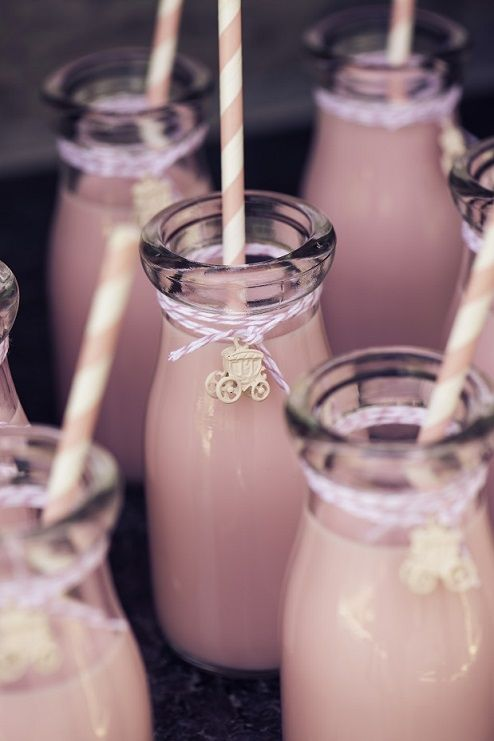 Super cute milk bottles decorated with paper straws, twine and carriage embellishment. read more at http://partystock.ca/blog/fairytale-tea-party-bridal-shower/