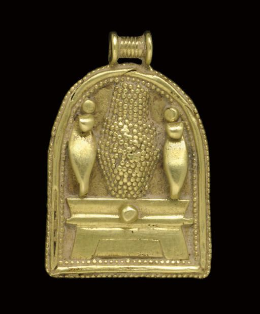 """A CARTHAGINIAN GOLD PENDANT   CIRCA 6TH CENTURY B.C.   Shrine-shaped, in Egyptianizing style, with uraei flanking a granulated """"bottle idol"""" upon an altar with a cavetto cornice, a large granule in the center of the cornice, bordered with two rows of granulation framing plain wire, surmounted by a ribbed suspension loop  1 3/16 in. (3 cm.) long"""